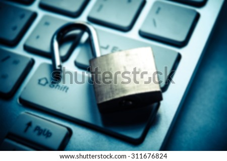 Abstract blurred background of a security lock on computer keyboard - computer security breach concept - stock photo