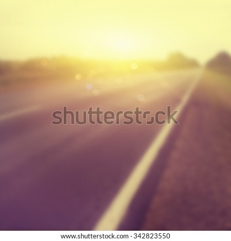 Abstract blurred background of country road at sunset. - stock photo