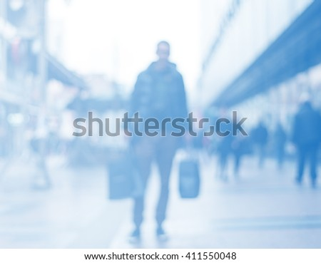 abstract blurred background of people on the street, unrecognizable silhouette of man holding bags after shopping