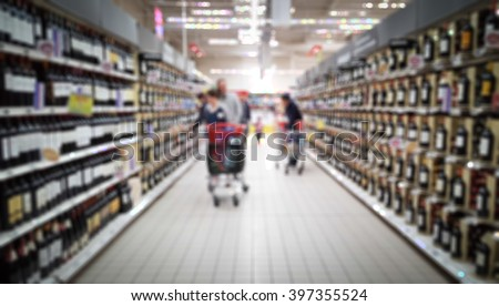 Abstract blurred background : People in a Bordeaux, wine shop with their shopping carts, a lot of choices and varieties