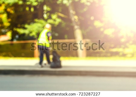 Abstract blurred background  - road sweeper worker cleaning city street with broom tool.