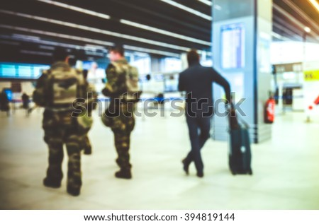 Abstract blurred background : Soldiers on patrol in airport terminal for Vigipirate Plan against terrorism in France. Airline passenger with luggage watch a flight information board. Security concept  - stock photo