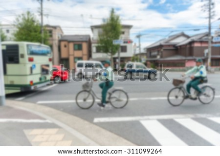 abstract blurred background Unidentified police man riding a bike  across crosswalk in japan. - stock photo