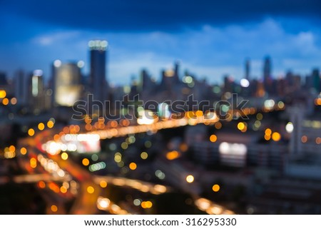 Abstract blurred bokeh city freeway with city background during twilight - stock photo