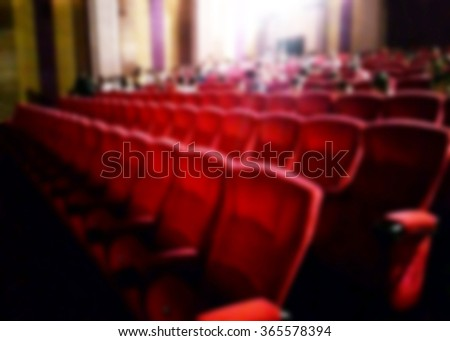 Abstract blurred dark background. Cinema with empty comfortable red seats and projector. The atmosphere in the theater before the Movies start. - stock photo
