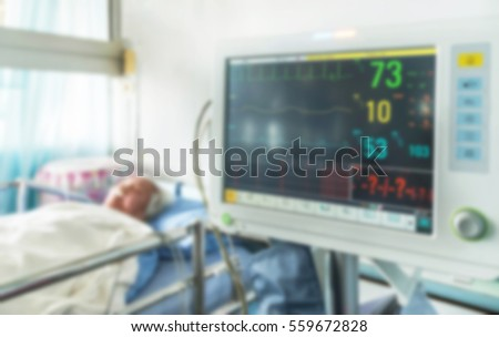 Abstract blurred digital device for measuring blood pressure monitor with elderly patient sleep on the bed in hospital ward room