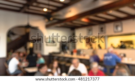 Abstract blurred French restaurant interior in French Quarter of New Orleans, Louisiana, US. People enjoying cafe, Creole cuisine, Cajun food. New Orleans deeply tied to French food culture. Panorama.
