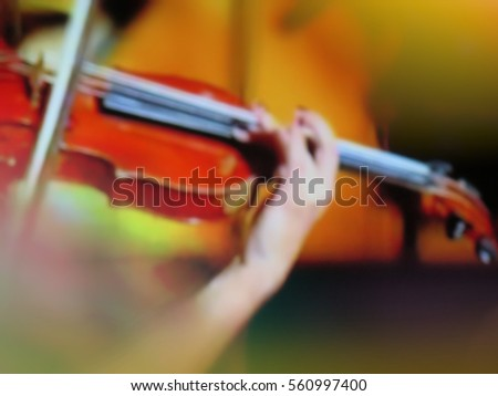 abstract blurred image. Actor violinist playing the violin strings. Musician plays a musical instrument on the concert stage