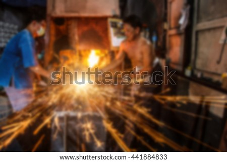 Abstract blurred image of people hit a steel knife by antique process in steel plant