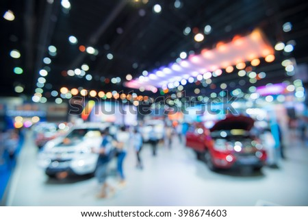 Abstract blurred image of people in cars exhibition show