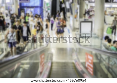 Abstract blurred image of people moving up or down on escalator in airport. - stock photo