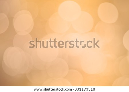 abstract blurred of golden metal color backgrounds with circle lights.blur of soft bokeh circle light christmas festive backdrop concept:blur gold yellow in warm tone colored backdrop concept. - stock photo