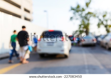 Abstract blurred people and car in parking area - stock photo