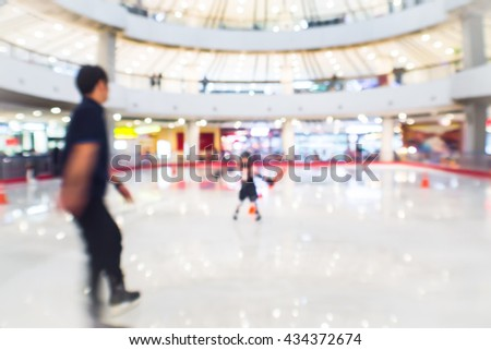 abstract blurred people playing at ice skating rink in the mall department store. - stock photo
