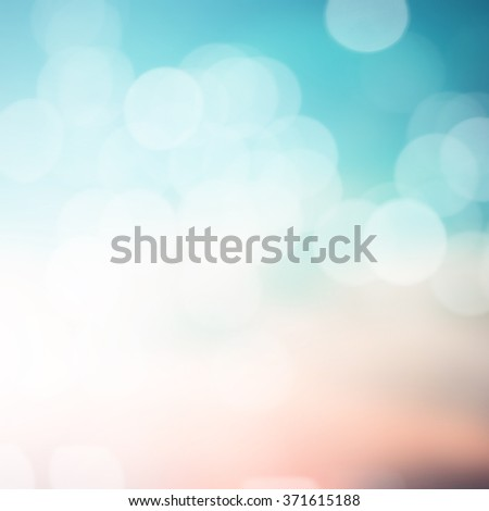 abstract blurred sunset background with circle lights in pastel color tone color.blur of bokeh sparkle of Christmas backdrop concept.blurry glitter shine decoration banner template:sunshine of summer.