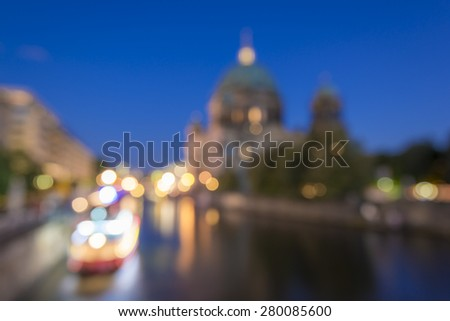 abstract blurry background of Berlin Cathedral (Berliner Dom) and tour boat on Spree River at evening, Berlin Mitte, Germany, Europe  - stock photo