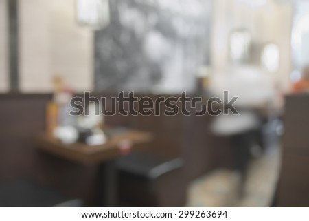 Abstract blurry dark brown restaurant interior table during dining time with unrecognizable waitress - stock photo