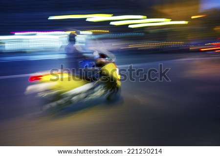 Abstract blurry image of a scooter driving at night. - stock photo