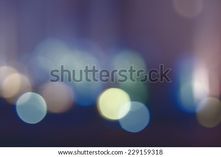 Abstract bokeh background. De-focused lights low saturation color. Pattern of blurred spots of lights glowing in the night. - stock photo