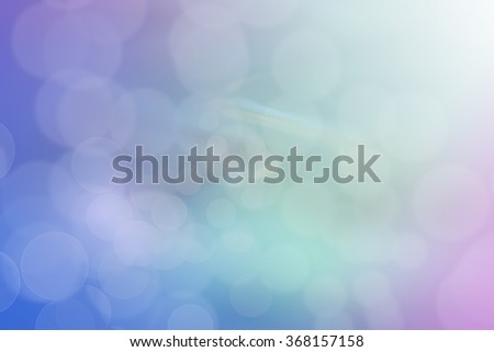 Abstract bokeh background in shades of blue, teal, green and purple.