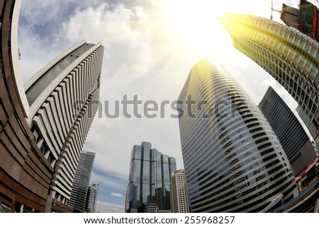 Abstract business background with office building and Sunbeam on sky, shot with a Fisheye lens.