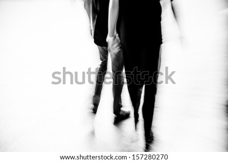 abstract business people walking on city street, black and white motion blurred. - stock photo