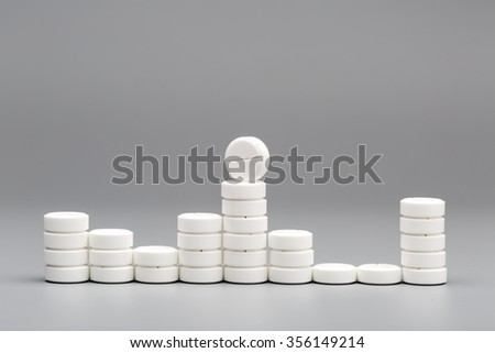 Abstract chart of white pills on a gray background - stock photo