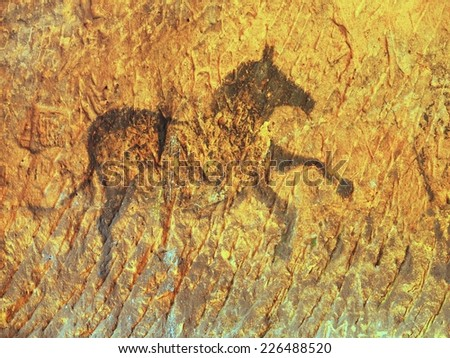 Abstract children art in sandstone cave. Black carbon paint of horses on sandstone wall, copy of prehistoric picture.  - stock photo