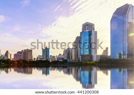 Abstract city reflection river on sunrise. Panoramic and perspective wide angle view to steel light blue background of glass high rise building skyscraper commercial modern city of future.pastel tone. - stock photo