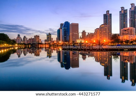 Abstract city reflection river on sunrise. Panoramic and perspective wide angle view to steel light blue background of glass high rise building skyscraper commercial modern city of future.