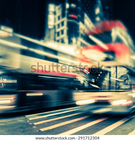 Abstract cityscape blurred background, art toning. Night view of modern city street with moving transport and illuminated skyscrapers. Hong Kong