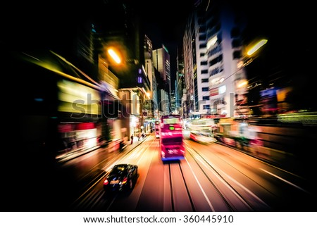 Abstract cityscape traffic background with red tram. Motion blur, art toning. Moving through modern city street with illuminated skyscrapers. Hong Kong - stock photo