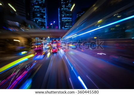 Abstract cityscape traffic background with red tram under the bridge. Motion blur, art toning. Moving through modern city street with illuminated skyscrapers. Hong Kong - stock photo