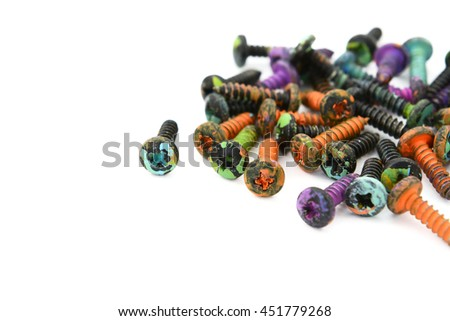 Abstract close-up of a heap of crosshead screws, covered in paint splatters, on a white background - stock photo
