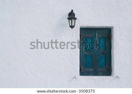 Abstract close-up of Santorini home wall, window and lamp. - stock photo