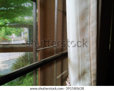 abstract close up part of wooden window and curtain with mosquito wire screen and Curved steel in house - stock photo