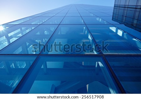 Abstract closeup of the glass-clad facade of a modern building covered in reflective plate glass - stock photo
