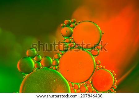 Abstract cluster of green and orange water bubbles aligning in front of a blurry background - stock photo