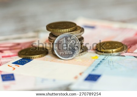 Abstract. Coin one ruble and the European currency: banknotes of five and fifty euro coins - stock photo