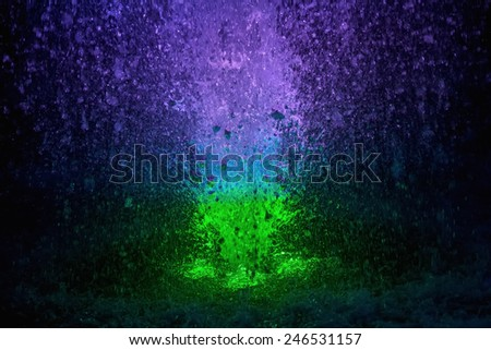 Abstract colorful fountain splashes green and blue color of water drops on a black background. motion blur