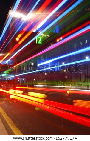 Abstract colorful light trails from traffic in the city center - stock photo