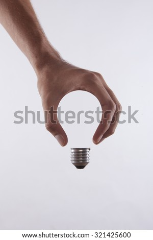 abstract conceptual image of a male's hand holding a light bulb shape - stock photo