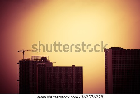 Abstract construction cranes and building silhouettes over sun at sunrise. vintage picture tone. - stock photo