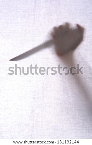 Abstract crime background. Silhouette of someone holding knife - stock photo