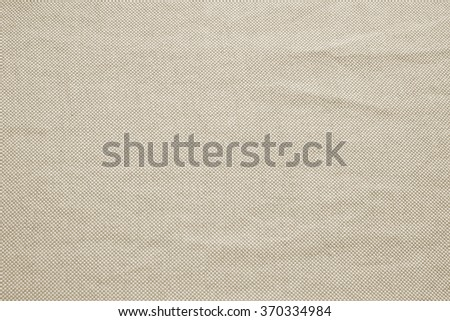Abstract crumpled orange colored fabric texture backgrounds:creased burlap fabric textures in bright beige sepia color tone.wrinkle vintage garment backdrop. - stock photo