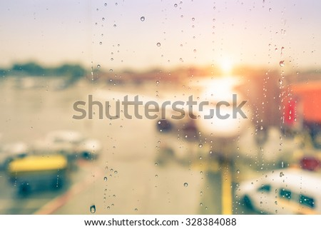 Abstract defocused bokeh of airplane at airport gate with sun coming out after the rain - Modern travel concept and wander lifestyle at sunset - Focus on raindrops with warm vintage filtered look - stock photo