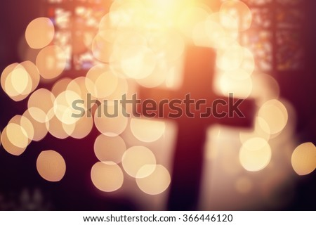 Abstract defocussed cross silhouette in church interior against stained glass window concept for religion and  prayer - stock photo