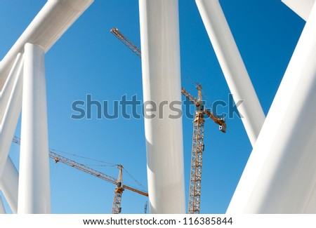 Abstract design of pipes. In background, high-rise construction cranes. - stock photo