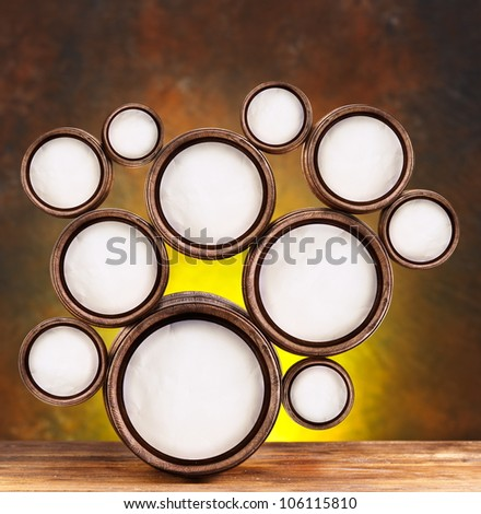 Abstract design of round shapes in the form of beer barrels on a dark yellow background. Inside the barrels textured watercolor paper. - stock photo