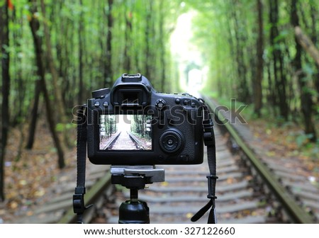 Abstract DSLR Camera on railway in forest - stock photo